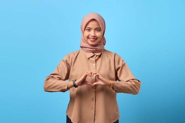 指の手でハートサインを作る陽気な若いアジアの女性の肖像画