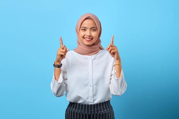 直接広告プロモーションを指している陽気な若いアジアの女性の肖像画