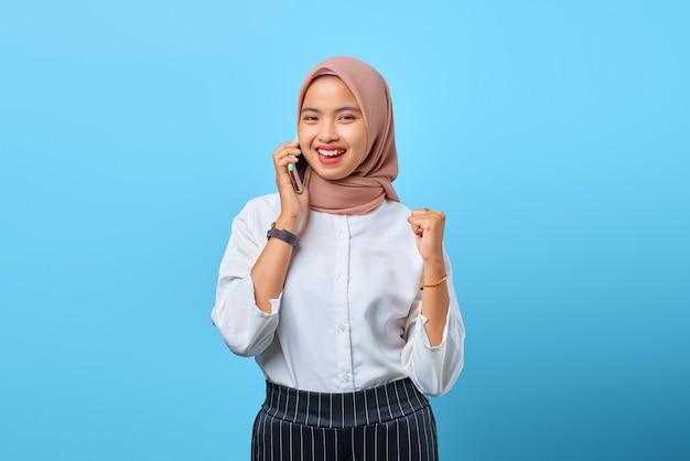 成功を祝って携帯電話で話している陽気な若いアジアの女性の肖像画