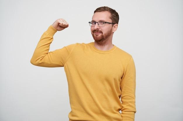 Портрет веселого молодого бородатого мужчины с каштановыми короткими волосами, уверенно выглядящего, демонстрирующего силу в поднятой руке, стоя в повседневной одежде