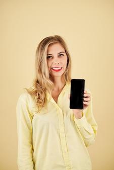 黄色で隔離のスマートフォンを示す陽気な若いブロンドの女性の肖像画