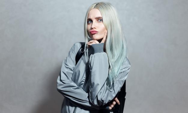 Портрет веселой молодой блондинки с голубыми глазами на серой поверхности.