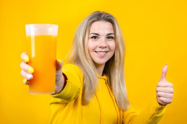 오렌지 주스 유리를 들고 쾌활한 젊은 금발의 여자의 초상화, 엄지 손가락을 표시, 노란색에 고립 된 웃는 소녀