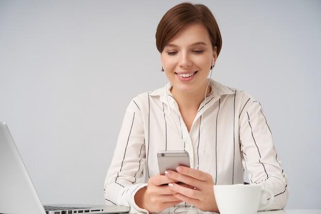 흰색에 앉아 메시지를 읽는 동안 광범위하게 웃고있는 동안 제기 손에 휴대 전화를 유지하는 짧은 유행 머리와 쾌활한 젊은 갈색 머리 여성의 초상화