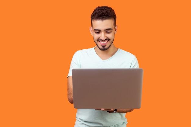 Портрет жизнерадостного молодого брюнет с бородой в белой футболке, печатающего электронную почту на ноутбуке и улыбающегося, читающего позитивное сообщение или просматривающего веб-страницы. закрытый студийный выстрел изолирован на оранжевом фоне