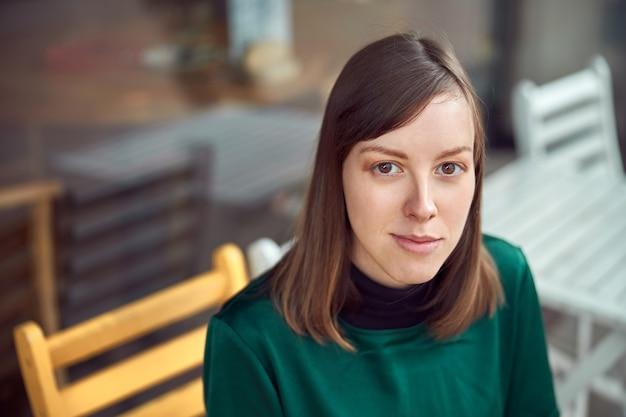 카페 밖에 앉아 녹색 옷을 입고 쾌활한 젊은 백인 여자의 초상화