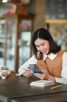 Портрет веселой молодой женщины студента колледжа, расслабляющейся в кафе