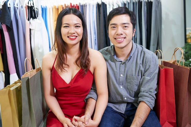 ショッピングバッグとデパートに座っているときに手をつないで陽気な若いカップルの肖像画