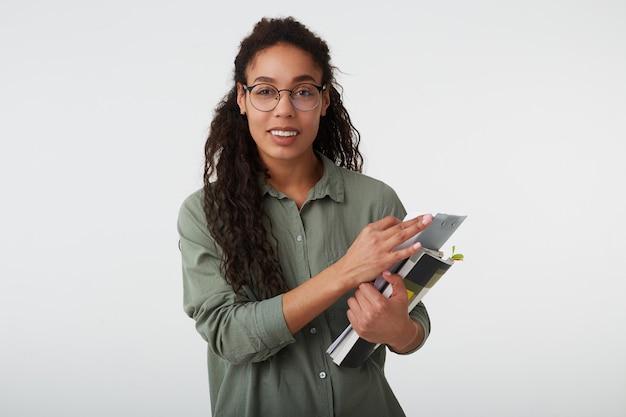 陽気な若い巻き毛のブルネットの暗い肌の女性の肖像画、カジュアルな髪型で教科書を上げた手で維持し、白で隔離の広い笑顔