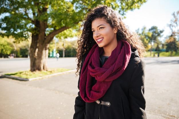 スカーフを身に着けている陽気な若い暗い肌の巻き毛の女性の肖像画脇を見てください。