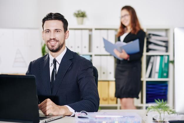 彼のオフィスの机でラップトップに取り組んでいる陽気な若い起業家の肖像画、彼のアシスタントはバックグラウンドでドキュメントを検索しています