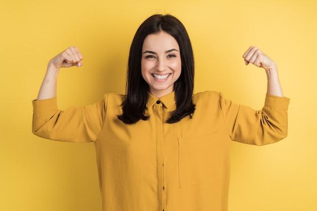 Портрет веселой молодой девушки, сгибающей бицепсы, изолированной на желтой стене