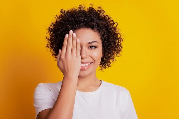 黄色の背景に陽気な若い女の子の手のひらの半分の顔の肖像画