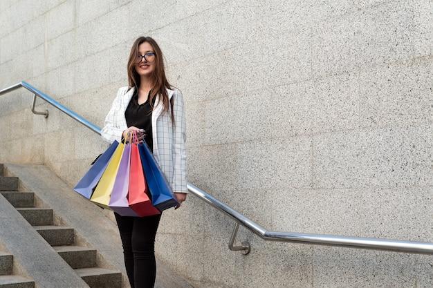色とりどりの買い物袋を持つ陽気な少女の肖像画。お土産を持った観光客。