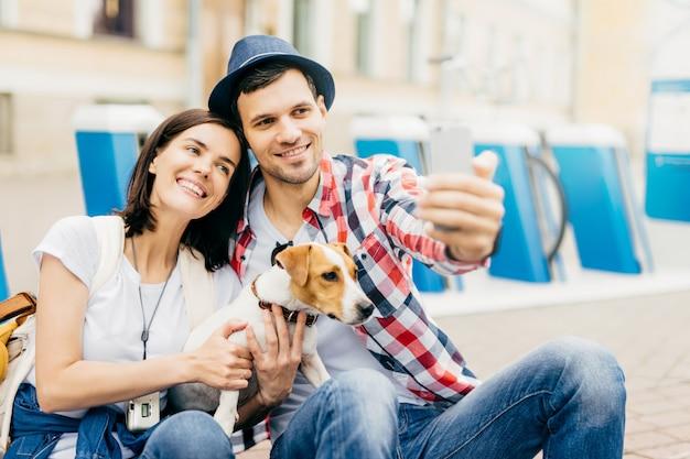 ハンサムな夫に傾いて、selfieのポーズをしながらカメラにうれしそうに笑っている陽気な若い格好良い女性の肖像画。
