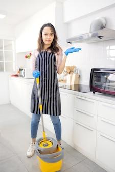 Портрет веселой молодой домохозяйки, держащей моющие средства Premium Фотографии
