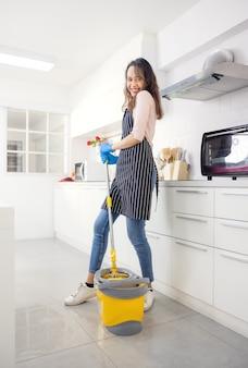 Портрет веселой молодой домохозяйки, держащей моющие средства