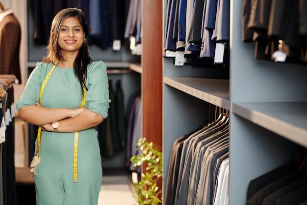 腕を組んで店に立ってカメラを見ている陽気な若いインドの店員の肖像画
