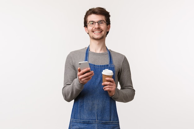 쾌활한 젊은 남성 직원의 초상화는 테이크 아웃 컵과 스마트 폰 미소 카메라를 들고 자신의 커피 숍에서 할인을받을 휴대 전화 애플 리케이션 프로모션 코드를 사용하는 것이 좋습니다