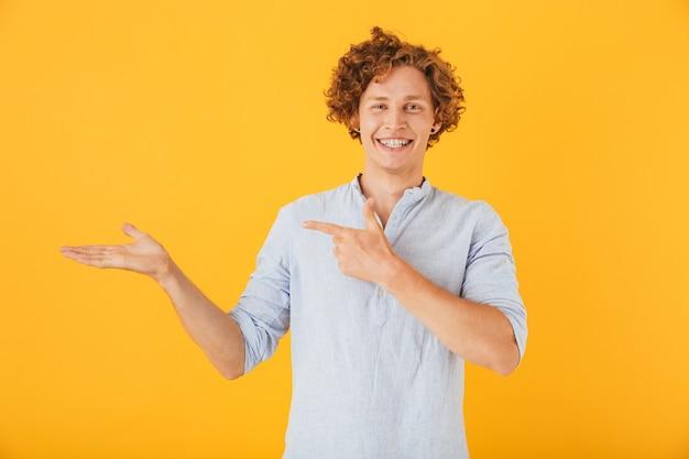 Портрет веселого молодого человека, рекламирующего и держащего copyspace под рукой, изолированного на желтом фоне
