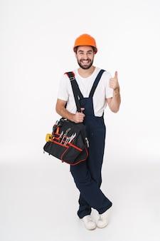 親指を立てるジェスチャーを示す機器の楽器とバッグを保持している白い壁の上に隔離されたヘルメットの陽気な若い男のビルダーの肖像画。