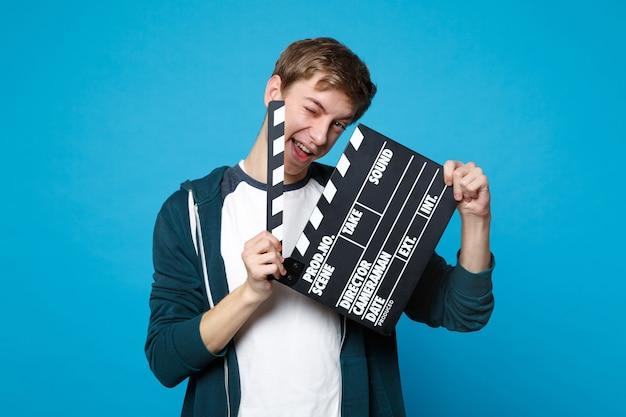 Портрет веселого молодого человека в повседневной одежде держит классический черный фильм, делая с 'хлопушкой', изолированную на синей стене. люди искренние эмоции, концепция образа жизни.