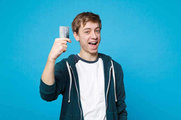 青い壁に分離されたクレジット銀行カードを保持しているカジュアルな服を着た陽気な青年の肖像画。人々の誠実な感情、ライフスタイルのコンセプト。