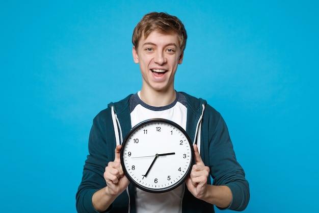 Портрет веселого молодого человека в повседневной одежде, держащего круглые часы, изолированные на синей стене. время уходит. люди искренние эмоции, концепция образа жизни.