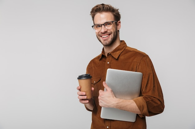 Портрет веселого молодого человека в очках позирует с ноутбуком и бумажным стаканчиком, изолированным над белой стеной