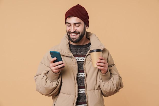 Портрет веселого молодого человека в зимней одежде, держащего кофейную чашку и мобильный телефон, изолированный на бежевом