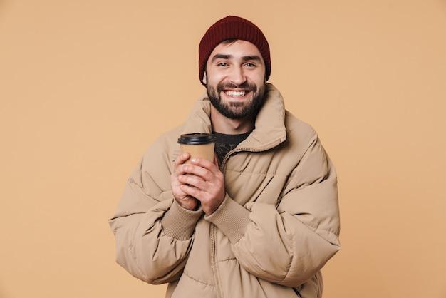 Портрет веселого молодого человека в зимней куртке и шляпе, улыбающегося во время питья кофе, изолированного на бежевом