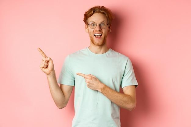 ピンクの背景の上に立って、眼鏡をかけ、左上隅に指を指して、笑顔で、赤い髪の陽気な若い男の肖像画。
