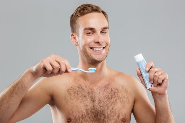 Портрет веселого молодого человека с зубной щеткой и зубной пастой