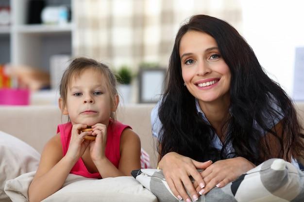 陽気な若い母親と居心地の良いソファで休んでいる娘の肖像画。ベーグルを保持している幸せな女の子。ホームインテリア。家族の時間と子供の頃のコンセプト