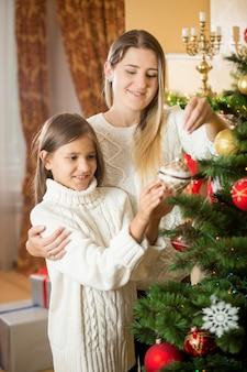 家で娘とクリスマスツリーを飾る陽気な若い母親の肖像画