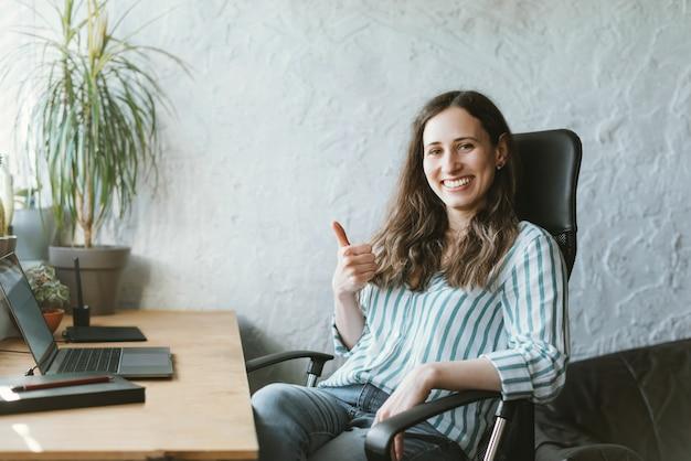 Портрет жизнерадостного молодого офиса wonan сидя перед столом и показывая большие пальцы руки вверх