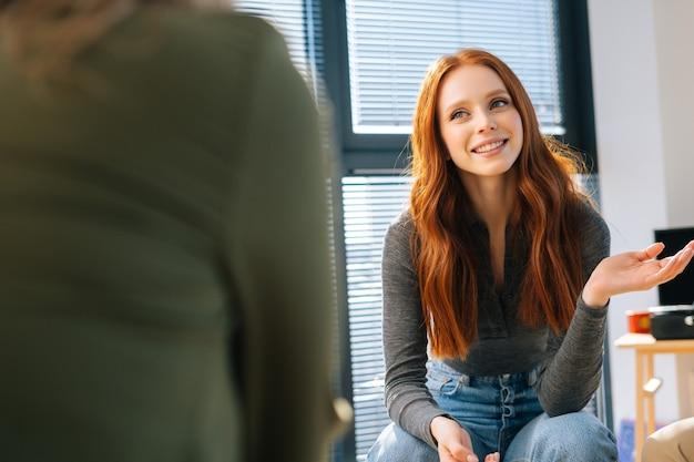 Портрет веселой молодой рыжеволосой женщины, слушающей коллег во время мозгового штурма стартап-проектов. бизнесмены разговаривают во время семинара по тимбилдингу в современном офисе.