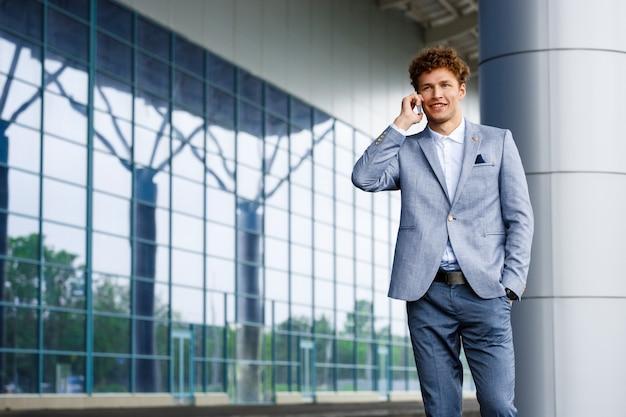 Портрет веселый молодой рыжий бизнесмен, разговаривает по телефону