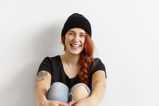 Портрет веселой молодой рыжей европейской женщины с косой, одетой в стильную одежду