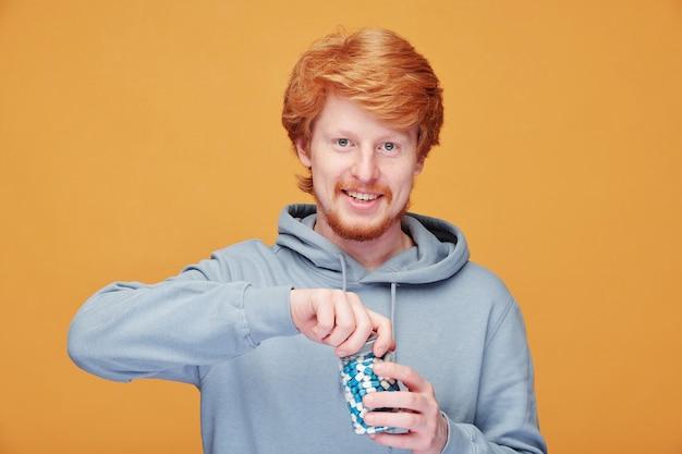 彼の免疫の世話をしながらビタミンボトルを開くパーカーで陽気な若い赤毛の男の肖像画