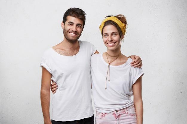 陽気な若い女性と白いtシャツに身を包んだ男の肖像画。抱き合って、広く見て笑っています。