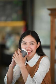 Портрет веселой молодой женщины, держащей чашку кофе и улыбающейся, сидя на своем рабочем месте.