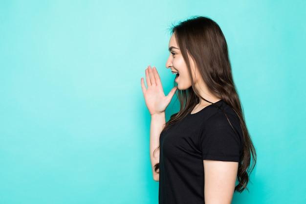 明るい青い壁の壁に隔離された口の近くの手で叫んでいる緑のカジュアルな服を着た陽気な若い女性の肖像画。人々のライフスタイルの概念。コピースペースのモックアップ Premium写真