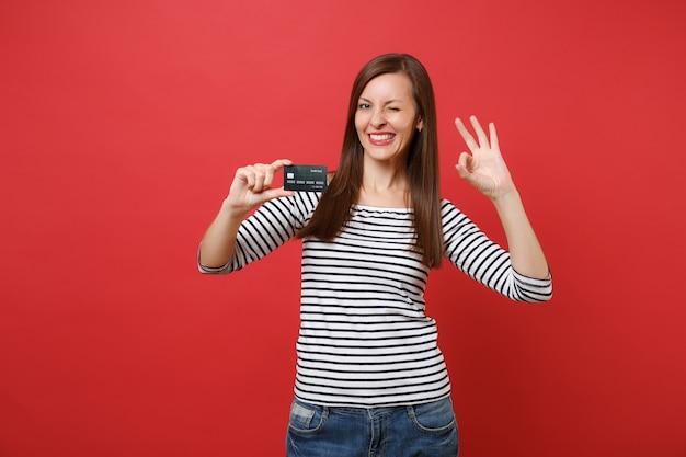 真っ赤な壁の背景に分離されたクレジットカードを保持しているokサインを示す点滅する縞模様の服を着た陽気な若い女性の肖像画。人々の誠実な感情、ライフスタイルのコンセプト。コピースペースをモックアップします。