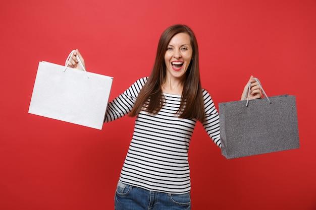 줄무늬 옷을 입은 쾌활한 젊은 여성의 초상화는 빨간색 벽 배경에서 격리된 쇼핑 후 구매한 패키지 가방을 들고 있습니다. 사람들은 진심 어린 감정, 라이프 스타일 개념입니다. 복사 공간을 비웃습니다.