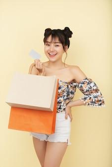 多くの購入でクレジットカードや買い物袋を示す陽気な若い女性の肖像画