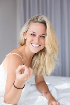 Портрет веселая молодая женщина, сидя на кровати