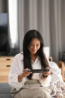 Портрет веселой молодой женщины, сидящей на софе в гостиной и играет в видеоигру.