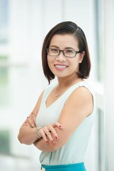 Портрет веселый молодой женщины, стоя сложа руки у окна
