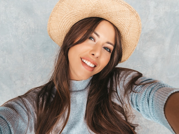写真selfieを取り、モダンな服と帽子を着て陽気な若い女性の肖像画。